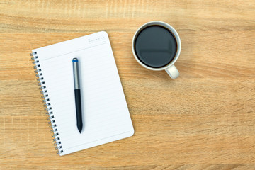 A cup of coffee with note and pen on working table with copy space top view.