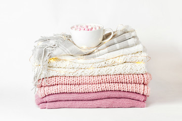 Stack of warm clothes sweaters and plaid with cup of coffee.