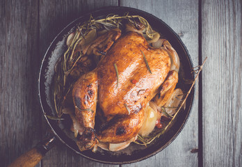 Roasted chicken in pan on the rustic wooden background. Selective focus. Toned image.