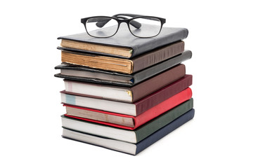 A stack of books with eyeglasses on a white background.