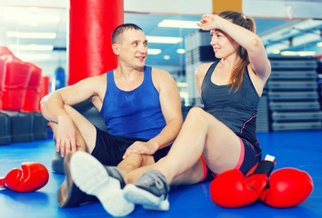 Female boxer is sitting with man and talking about healthy in gym.