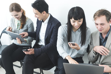 Group of people using various mobile devices.