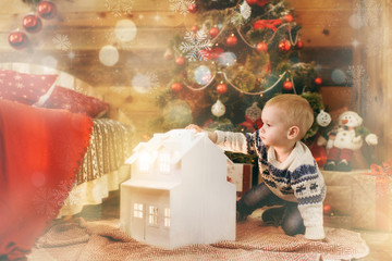 Happy little baby boy sitting at the Christmas tree with a toy white house in wooden room at home. Child good mood. New Year. Lifestyle, family and holiday 2018 concept. Magical highlight bokeh effect