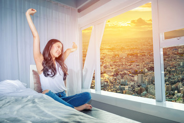 Beautiful woman stretch herself out on the couch in the morning in white bedroom with city view