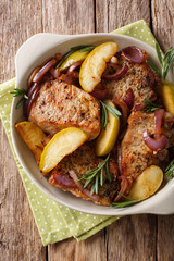 Spicy baked pork chop with green apples, onion and rosemary close-up in a baking dish. Vertical top view