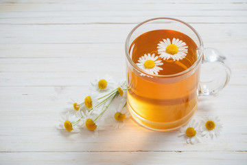 cup of tea with chamomile on white wooden background
