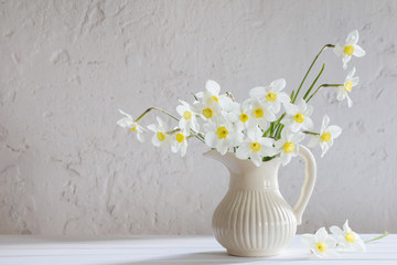 daffodils in jug on white background