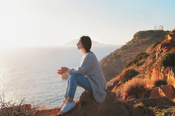 Traveler young woman sits on a cliff of cape Sounion and enjoys the moment.