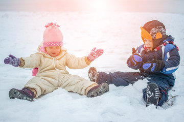 Cheerful children having fun and playing in the snow during cold winter day.