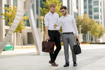 Business colleagues in shirt walking outdoors