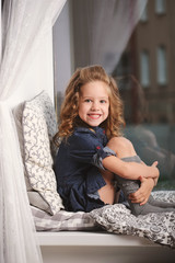 little girl on the windowsill at home