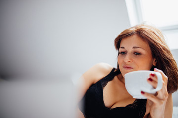 Young caucasian female laying in bed drinking coffee