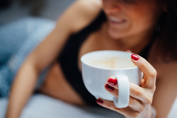 Close-up of women holding coffee cup in bed