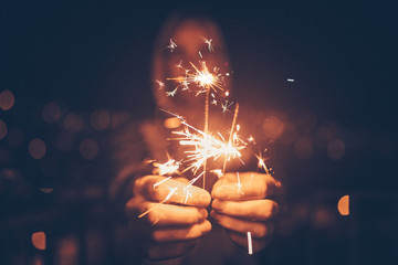 Man holding sparklers in his hands