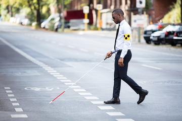Blind Man Wearing Armband Walking With Stick