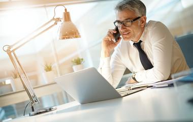 Businessman in office talking on smartphone