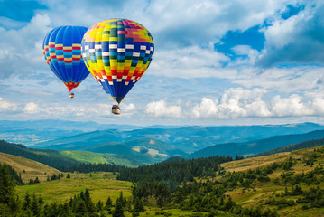 Colorful hot-air balloons flying over the mountains. Artistic picture. Beauty world.