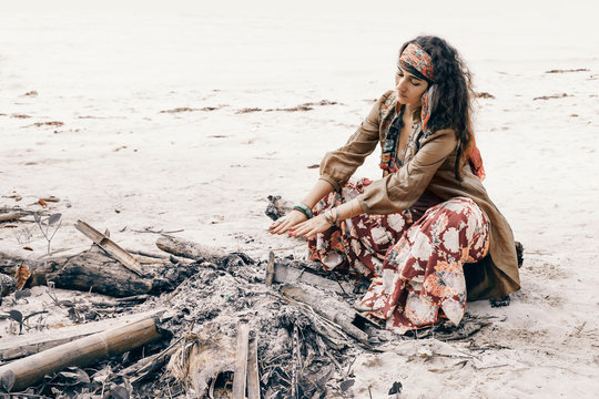 beautiful young gypsy style woman at fire