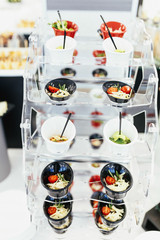 Circle with different cold salads in cups put on a candy bar