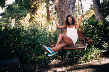 African Woman sitting on swing in the garden in summer