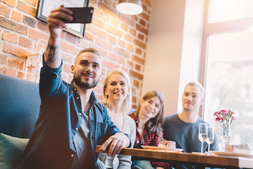 Group of people taking a selfie together in a restaurant.