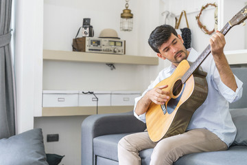Handsome man playing guitar in the living room.