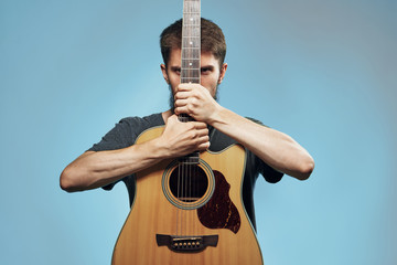 Man with a beard on a blue background holds a guitar, music, musical instruments