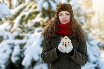 Woman holds wooden toy house in her hands. Energy and warm save concept