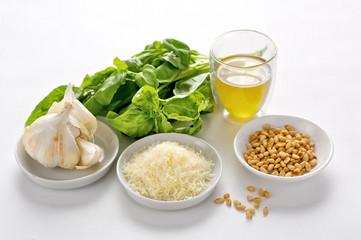 Zutaten für die Zubereitung von Pesto: Pinienkerne, Parmesan, Knoblauch, Olivenöl, Basilikum