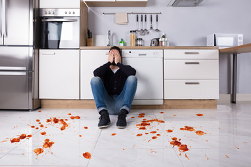 Man Sitting On Kitchen Floor With Spilled Food