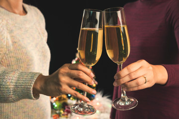 Beautiful two women holding glasses with champagne celebrating Christmas and gift boxes at corporate party and christmas lights, New Year Frame for your text