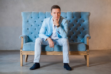 young elegant man in suit sits on arm chair