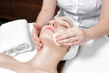 beautician cleanses the skin woman with a sponge.