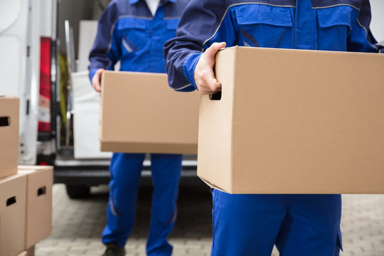 Close-up Of Two Movers Carrying Cardboard Box