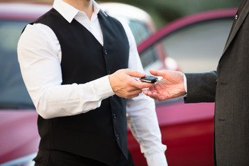 Valet Giving Car Key To Businessperson