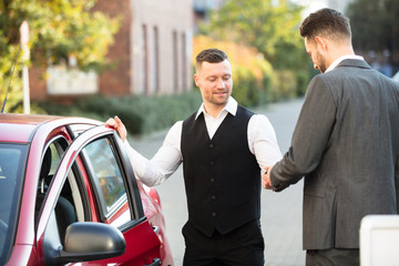 Smiling Valet And Businessperson Standing Near Car