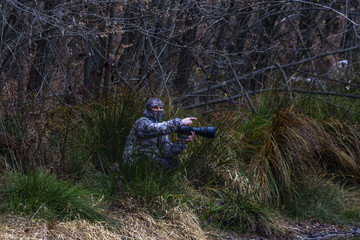 professional photographer with camouflage outfit in nature