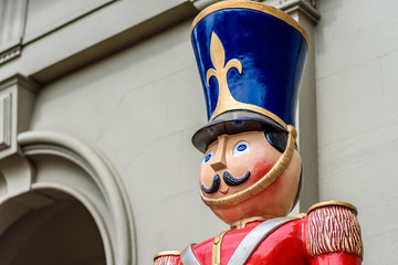 A life sized statue of a christmas toy soldier with a red coat and blue hat stands guard in front of a building