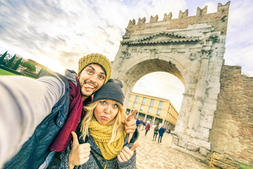 Happy hipster couple taking selfie at european city trip on winter clothes - Fun concept with alternative fashion world travelers - Handsome boyfriend with caucasian girlfriend - Warm afternoon filter