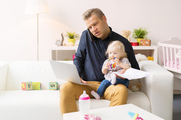 Father multitasking by babysitting and working on computer at the same time
