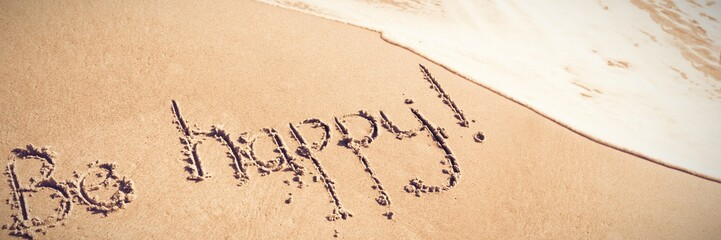 Be happy text written on sand