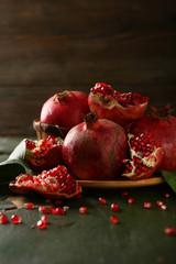 Ripe and sweet pomegranates on dark wood