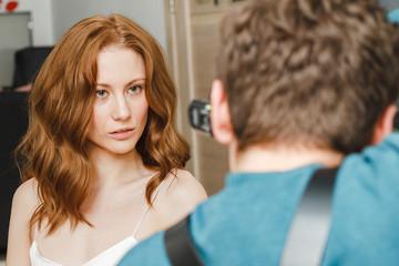 Man photographer shooting female model in studio