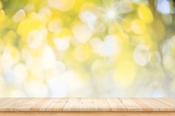 Empty wood table with bokeh yellow background.