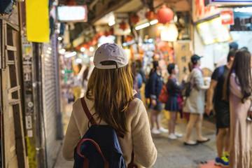 Young traveler walking at old street market at jiufen