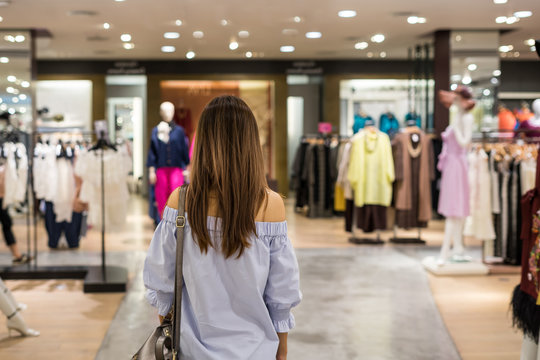 Young asian woman walking in clothes store at the mall
