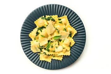 Plate of ravioli with pesto sauce on white background