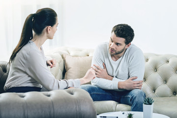 Psychological session. Handsome pleasant young woman looking at his therapist and talking to her while having a psychological session