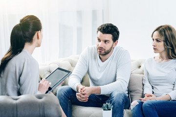 Will you help us. Nice depressed young couple looking at their therapist and sharing their problems while visiting a psychologist