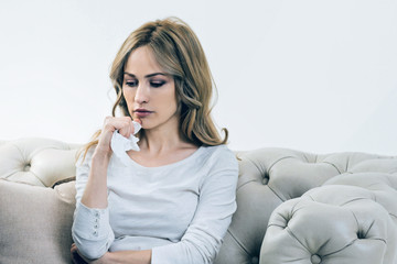 Personal problems. Unhappy depressed young woman holding a paper tissue and thinking about her problems while sitting on the sofa